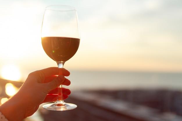 Een glas rode wijn bij zonsondergang.