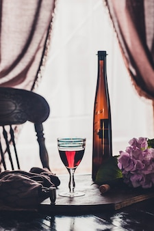 Een glas rode wijn en een fles op donkere houten