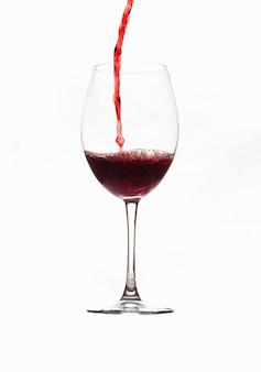 Een glas rode wijn in een dunne, heldere kristallen beker vullen