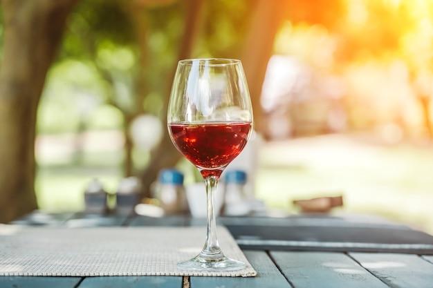 Een glas rode wijn op de tafel van een straatcafé, een zonnige zomerdag, zomerse levensstijl, ontspanning en...