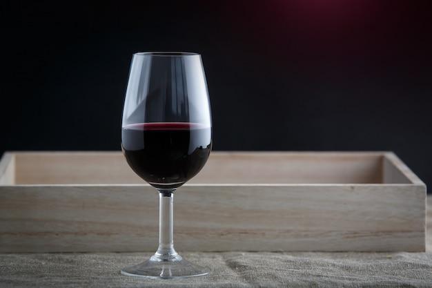Een glas rode wijn op zwarte achtergrond, stoffen staan onderaan
