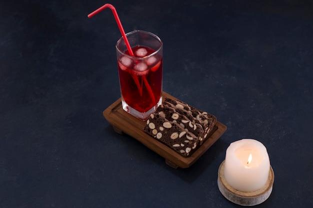 Een glas rood sap met cakeplakken op een houten schotel.