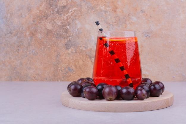Een glas rood sap met kersenbessen op een houten bord