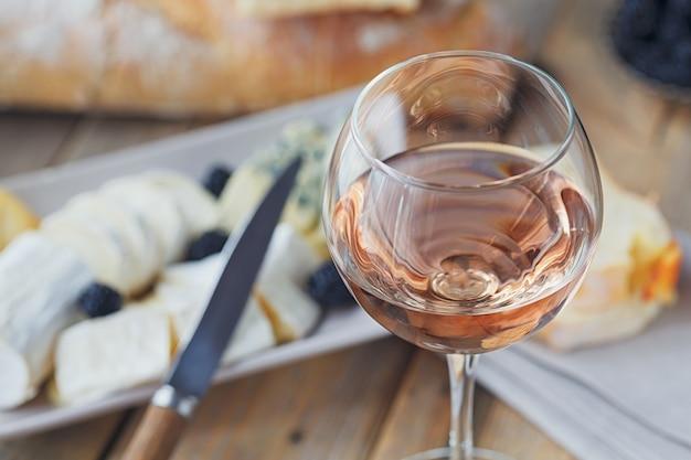 Een glas rose wijn geserveerd met kaasplankje, bramen en stokbrood. assortiment van kaas met bessen op houten achtergrond.