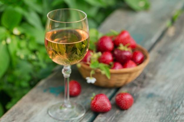 Een glas rose wijn geserveerd met verse aardbeien op houten