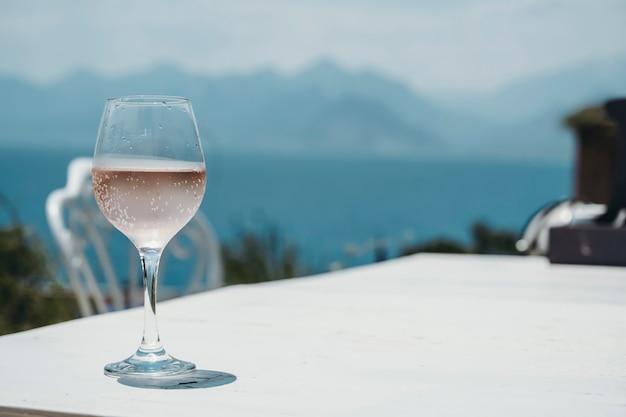 Een glas rose wijn op de tafel van een straatcafé tegen de achtergrond van de middellandse zee en...