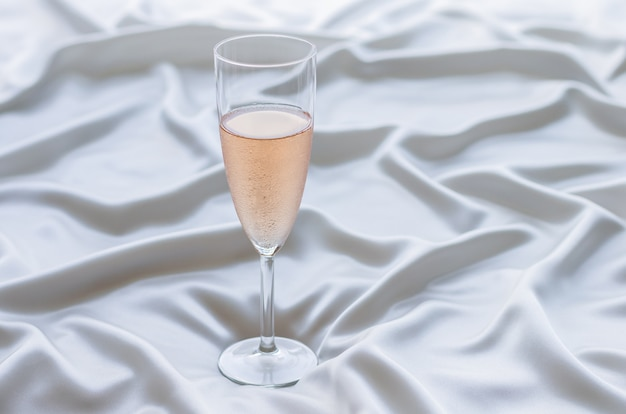 Een glas rose wijn op golvende satijnen doek