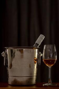 Een glas rose wijn op houten tafel met een fles in wijn koeler emmer.