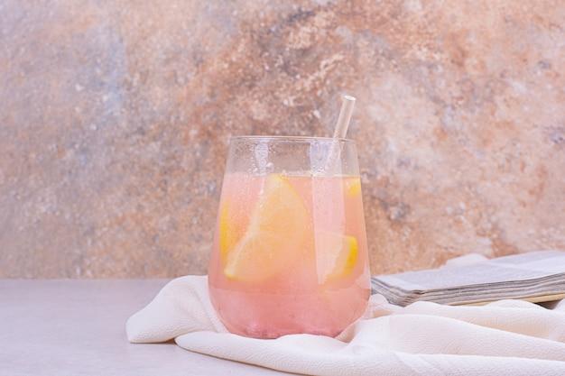 Een glas roze cocktail met schijfjes citroen.