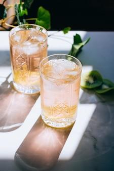 Een glas roze wijn in een kristalglas op marmeren, groene klimop en felle zon