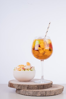 Een glas sap en fruitschaal witte tafel.