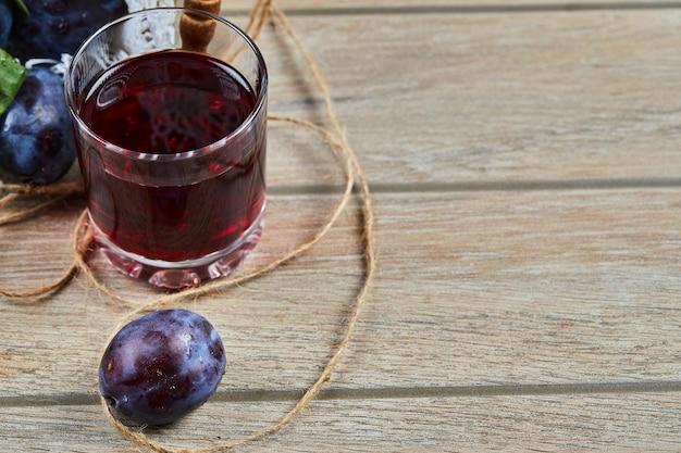 Een glas sap en tuinpruimen op houten tafel.