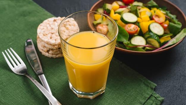 Een glas sap; gepofte rijstwafel en veganistische slakom op groen servet met bestek