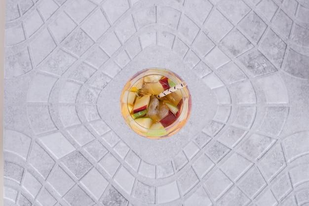 Een glas sap met fruitplakken op marmeren tafel.