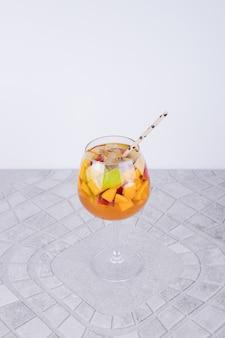 Een glas sap met fruitplakken op witte muur.