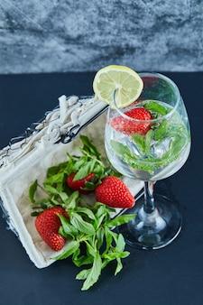 Een glas sap met hele vruchten binnen en mandje aardbeien op blauwe ondergrond