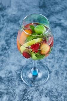 Een glas sap met hele vruchten binnen op blauwe ondergrond