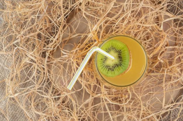 Een glas sap met kiwiplak en stro op jute