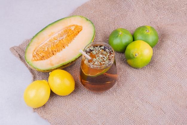 Een glas sap met kruiden en fruit eromheen