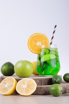 Een glas sap met plakjes fruit en vers fruit.