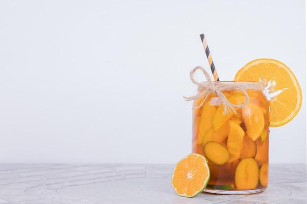 Een glas sap met plakjes fruit.
