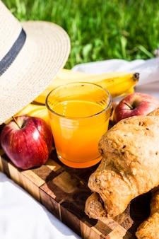 Een glas sap op een bord naast croissants en fruit op een zomerpicknick in de natuur