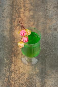 Een glas sappige groene limonade en rozen op marmeren muur.