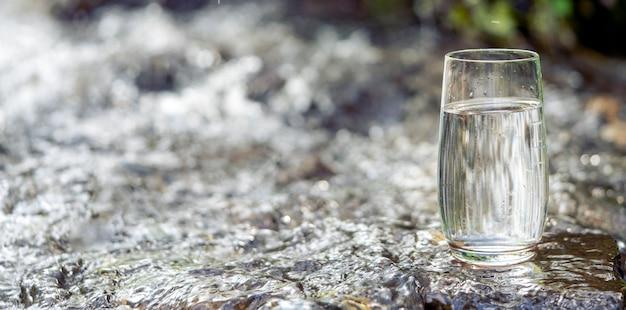 Een glas schoon transparant drinkwater in een transparant glas op een steen in een groen bos nabij...