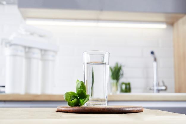 Een glas schoon water en filterpatronen op de huiskeuken