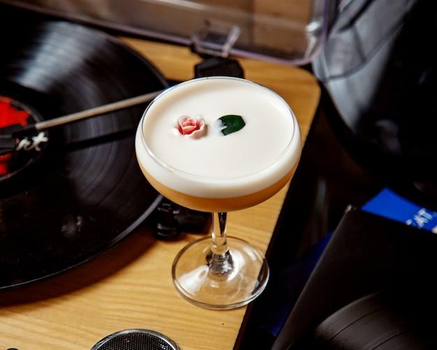 Een glas schuimende cocktail versierd met bloem en blad