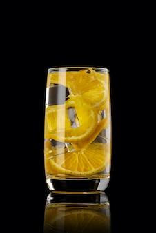 Een glas sinaasappellimonade op een zwarte
