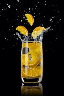 Een glas sinaasappellimonade, spetterend in verschillende richtingen en drie stukjes sinaasappel die in het glas vallen