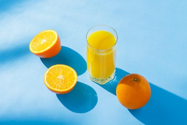 Een glas sinaasappelsap en sinaasappelen op een blauwe achtergrond. tropisch concept van vitaminen, zomer. natuurlijk licht. plat lag, bovenaanzicht.