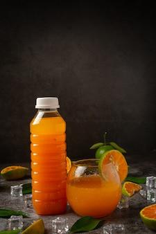 Een glas sinaasappelsap en vers fruit op de vloer met ijsblokjes.