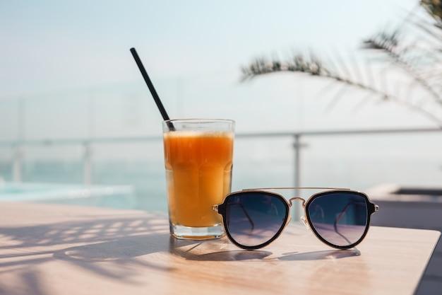 Een glas sinaasappelsap en zonnebril op de achtergrond van de zee.