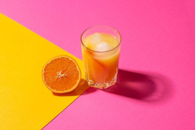 Een glas sinaasappelsap met ijs en half gesneden sinaasappel op een helder geel en roze