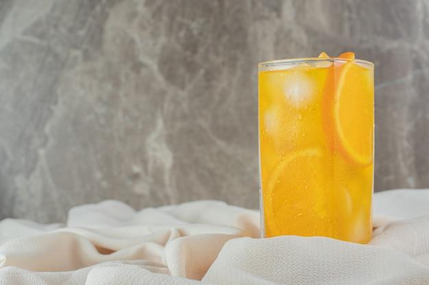 Een glas sinaasappelsap met ijsblokjes op satijnen doek