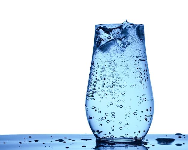 Een glas soda mineraalwater met ijsblokjes, bubbels en druppels close-up geïsoleerd op wit