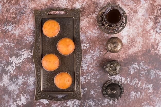 Een glas thee in etnische gerechten geserveerd met cupcakes