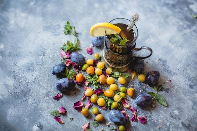Een glas thee met citroen en verspreide bessen - blauwe en gele pruimen