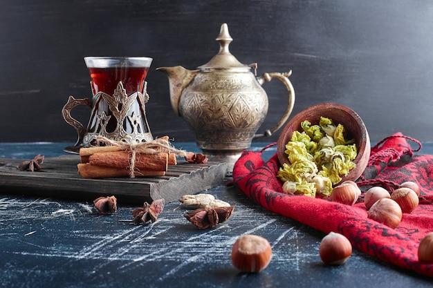 Een glas thee met kruiden en noten.