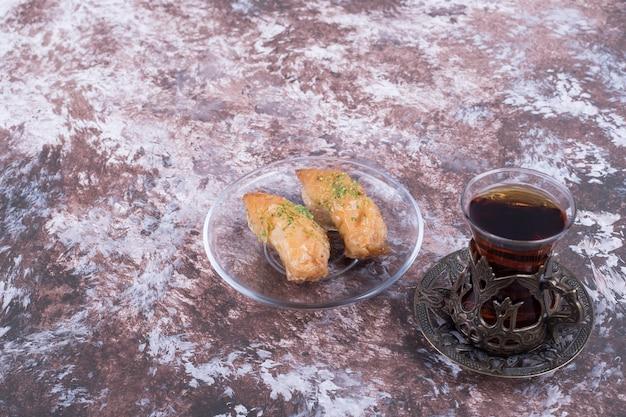 Een glas thee met turkse pakhlava in glazen schotel op marmeren tafel.