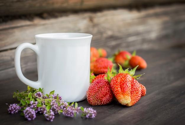 Een glas thee op een grijze houten achtergrond met aardbeien