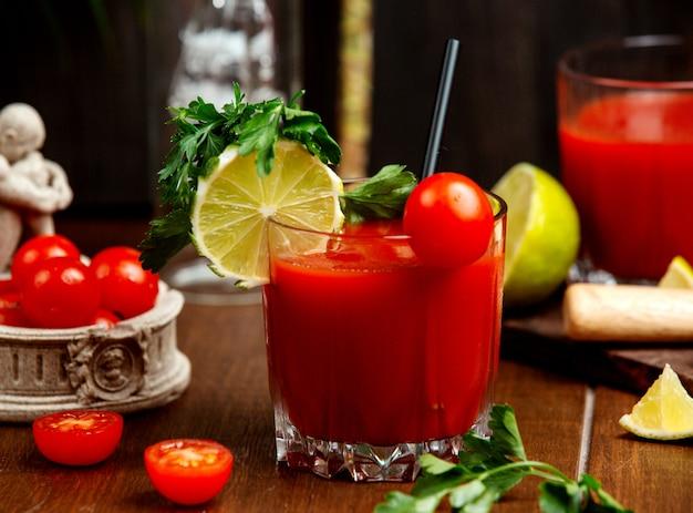Een glas tomatensap gegarneerd met cherrytomaat citroen en peterselie