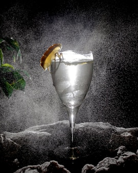Een glas transparante drank gegarneerd met schijfje citroen op donkere achtergrond met licht