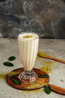 Een glas vanille milkshake met pistache hagelslag