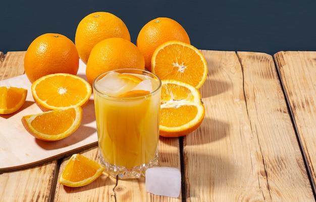 Een glas vers geperst sinaasappelsap met ijsblokjes en een houten plank