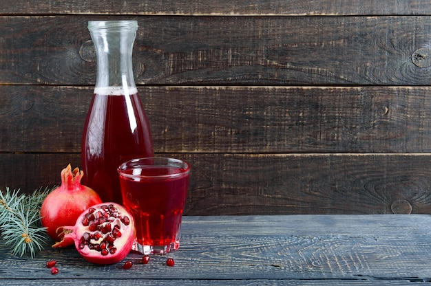Een glas vers granaatappelsap met rijpe granaatappelvruchten op houten tafel. vitamines en mineralen. gezond drankconcept. ruimte kopiëren.