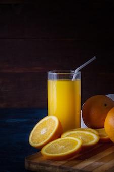Een glas vers sinaasappelsap met een buis, een houten kooktafel, stukjes sinaasappel, sinaasappels, witte doek op een donkerblauwe ondergrond