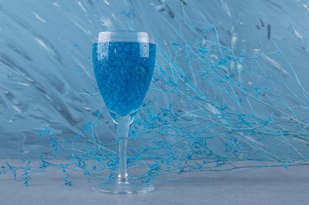 Een glas verse blauwe cocktail op grijze ondergrond